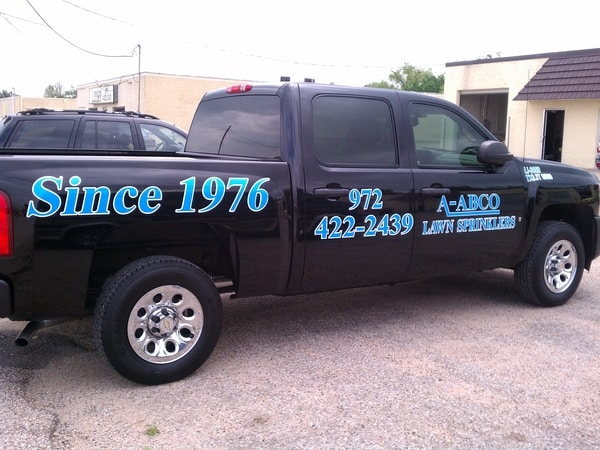 Black work truck with blue decals for lawn sprinkler company