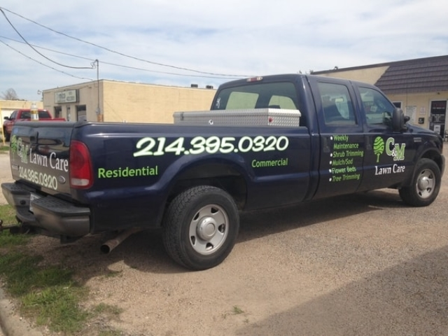 Back of blue work truck with decals for lawn care company