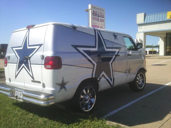 White and silver van with Dallas Cowboys logos