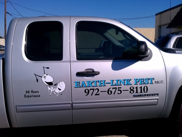 Silver truck with vinyl decals for pest control company