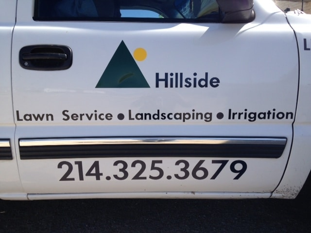 Side door of white truck with vinyl logo and lettering for lawn service company