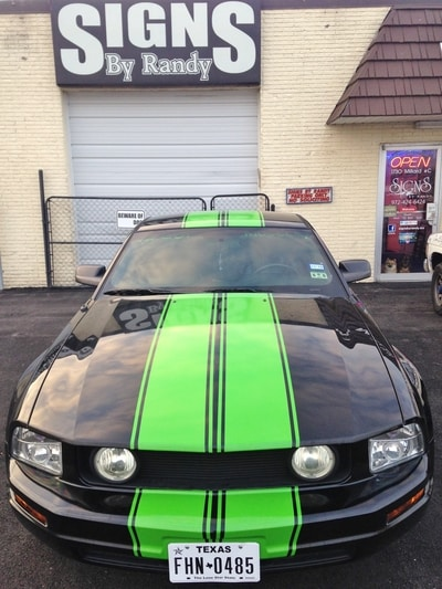 Black Ford Mustang with neon green racing strip vinyl decals in front of Signs by Randy storefront