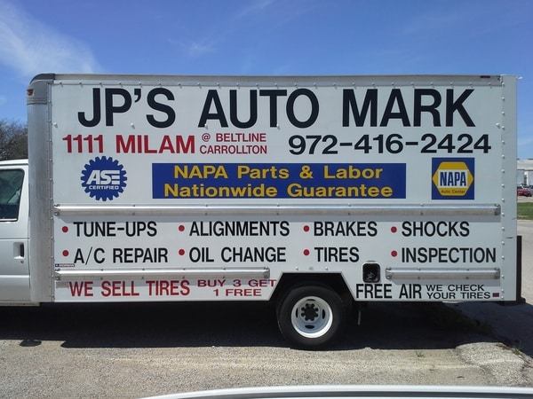 White moving van with decals for a car repair shop