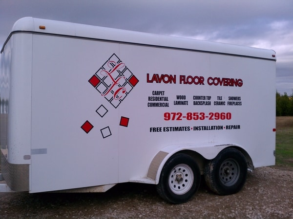 White covered trailer with vinyl decals for a floor covering company