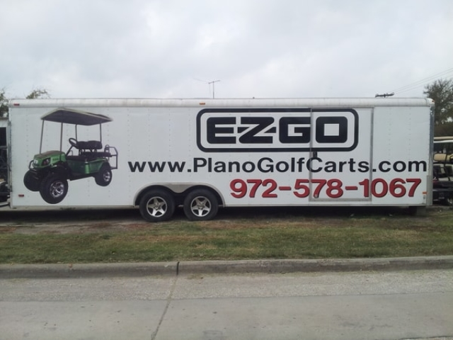 Long white auto trailer with vinyl car wrap decals for plano golf cart company