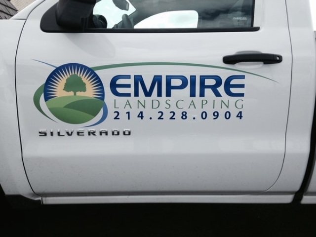 Door of white truck with logo decal for a landscaping company