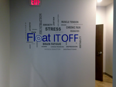 White wall in commercial building with decals of phrases such as float it off and brain fatique